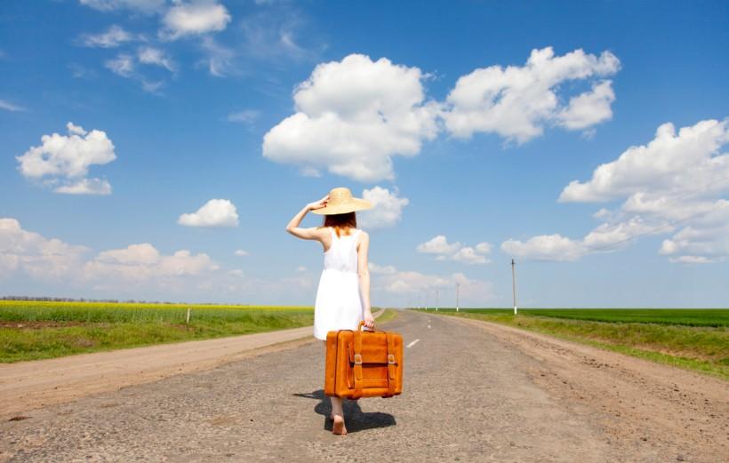 ragazza con una valigia in mezzo a una strada